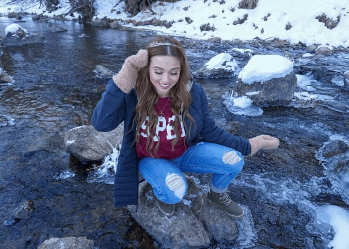 a girl on rock in a snow stream of water