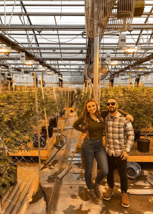 man and woman standing in front of a grow bed